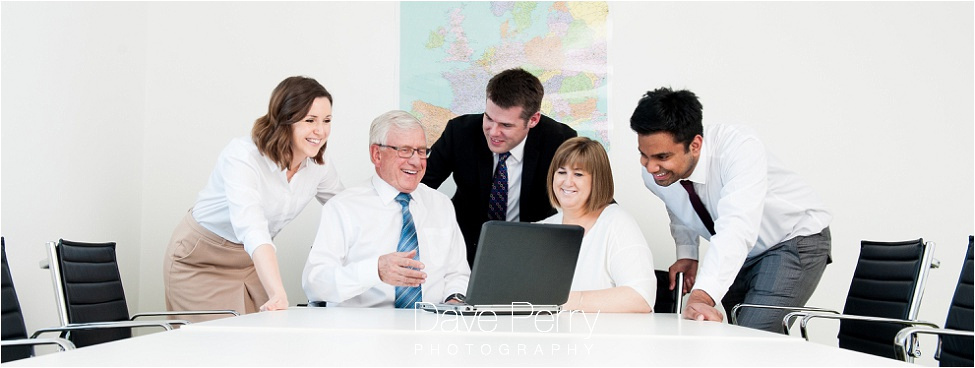 5 business people gathered around a laptop smiling in warwickshire