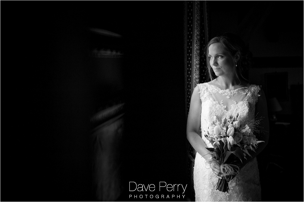 A bride holding flowers looking out a window at gorcott hall near redditch in Warwickshire