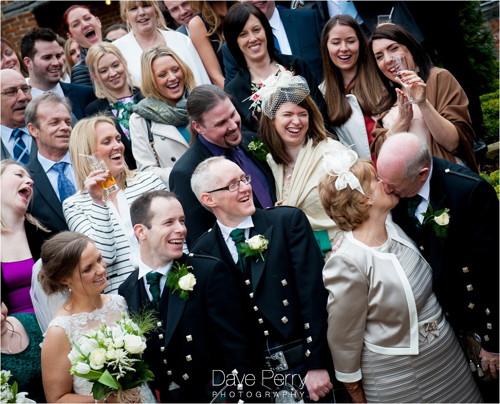 Mum and Dad kiss at Gorcott Hall while the wedding party look on in fits of giggles