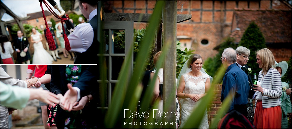 A bagpiper plays as people greet each other laughing whilst enjoying the wedding day at gorcott hall