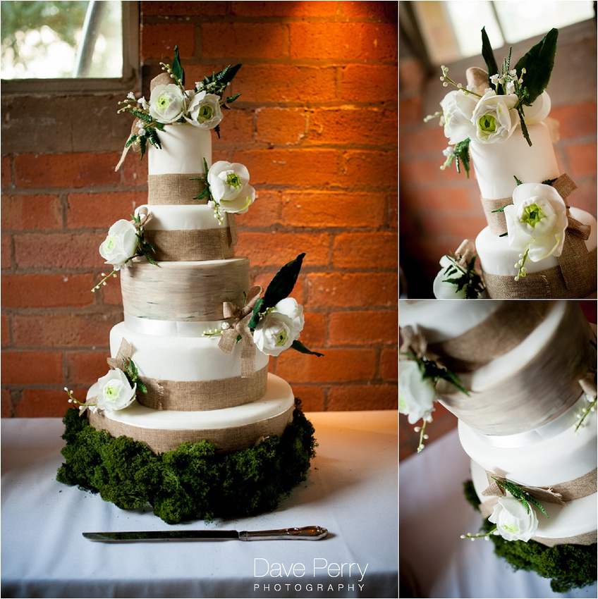 a wedding cake with flowers pinned to it that match the colour of the decoration for the wedding at gorcott hall
