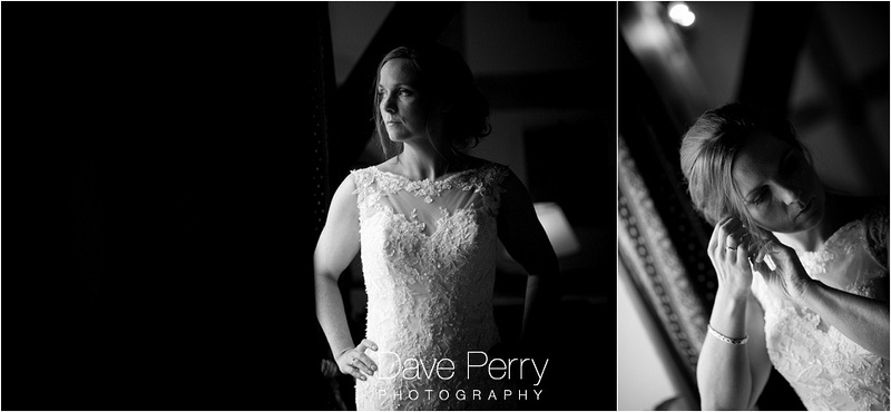 A bride looking out the window and adjusting her earrings shot at Gorcott hall in Redditch
