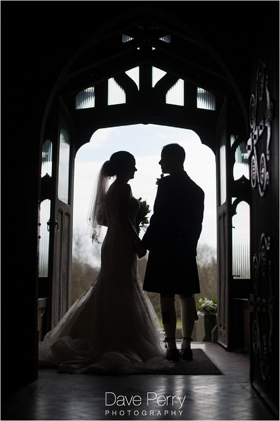 A bride and groom silouhette standing in the doorway at Gorcott hall after getting married